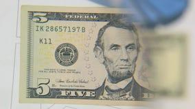 Betrachten Sie eine Banknote von fünf Dollar, eine Zunahme mit einer Lupe stock footage