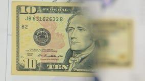 Betrachten Sie eine Banknote von zehn Dollar, eine Zunahme mit einer Lupe stock video