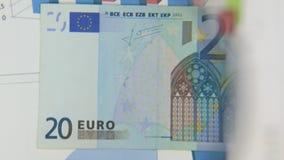 Betrachten Sie eine Banknote von zwanzig Euros, eine Zunahme mit einer Lupe stock footage
