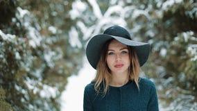 Betrachten Sie von hinten Dame im grünen Hut und in einem Mantel gehend um einen Winterwald die Mädchenblicke und -haltungen auf  stock video footage
