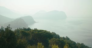 Betrachten Sie von oben genanntem dem hellen Nebel, der irgendwo Felsen, Berge und See in Montenegro bedeckt stock video footage
