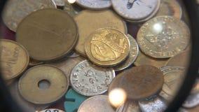 Betrachtungsmünzen unter Lupe stock video footage