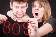 Young couple with broken heart and sos word. Betrayal and break up in relationship. Young couple arguing and holding red sos word sign symbol. Blonde women in royalty free stock photos