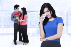 Betrayed woman and couple on the back Stock Photo