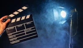 Betreiber, der clapperboard, Studiolicht auf Hintergrund hält lizenzfreies stockbild