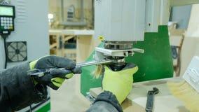 Betreiber einer modernen CNC-Holzbearbeitungsmaschine nimmt Anpassungen vor Arbeit vor Ändert den Schneider mit den Schlüsseln un stock footage
