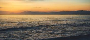 Betrekt blauwe hemel en gouden zonlichtzonsondergang op horizonoceaan, de stralenzonsopgang van de achtergrondzeegezicht dramatis stock foto's