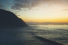 Betrekt blauwe hemel en gouden zonlichtzonsondergang op horizonoceaan, de stralenzonsopgang van de achtergrondzeegezicht dramatis stock fotografie