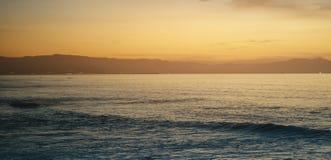 Betrekt blauwe hemel en gouden zonlichtzonsondergang op horizonoceaan, de stralenzonsopgang van de achtergrondzeegezicht dramatis royalty-vrije stock foto's