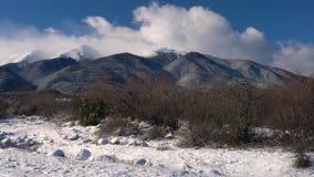 Betrekt het blazen door een blauwe hemel over een alpien die bergketenlandschap in sneeuw en sparren wordt behandeld stock videobeelden