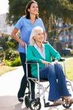 Betreuer, der ältere Frau im Rollstuhl drückt Stockbilder