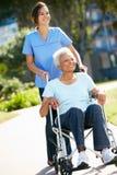 Betreuer, der ältere Frau im Rollstuhl drückt Stockfotos