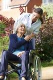 Betreuer, der ältere Frau im Rollstuhl drückt stockfoto