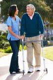 Betreuer, der älterem Mann mit gehendem Feld hilft Lizenzfreie Stockfotos