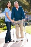 Betreuer, der älterem Mann mit gehendem Feld hilft Lizenzfreie Stockbilder