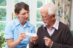 Betreuer, der älterem Mann mit Medikation hilft lizenzfreie stockfotografie