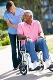 Betreuer, der älteren Mann im Rollstuhl drückt Stockfotos