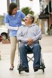 Betreuer, der arbeitsunfähigen älteren Mann im Rollstuhl drückt Stockbilder