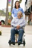 Betreuer, der arbeitsunfähigen älteren Mann im Rollstuhl drückt Lizenzfreie Stockfotos