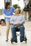 Betreuer, der arbeitsunfähigen älteren Mann im Rollstuhl drückt Stockfotografie