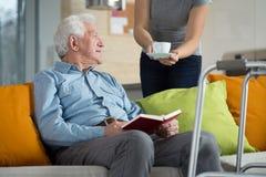 Betreuer, der arbeitsunfähigen Mannkaffee gibt Lizenzfreies Stockfoto