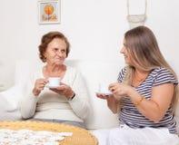 Betreuer, der eine Tasse Tee mit einer älteren Frau isst Stockbilder