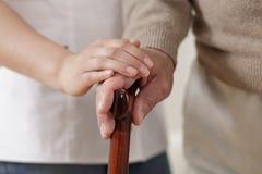 Betreuer, der Hand des alten Mannes hält Lizenzfreies Stockfoto