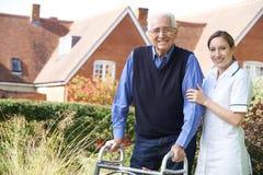 Betreuer, der älterem Mann hilft, in Garten unter Verwendung des gehenden Rahmens zu gehen Lizenzfreies Stockbild