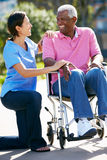 Betreuer, der älteren Mann im Rollstuhl drückt Lizenzfreies Stockbild