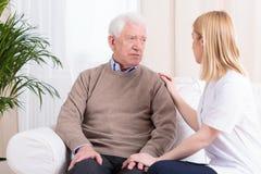 Betreuer, der älteren Mann stützt Lizenzfreies Stockfoto