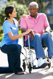 Betreuer, der unglücklichen älteren Mann im Rollstuhl drückt Stockfotos