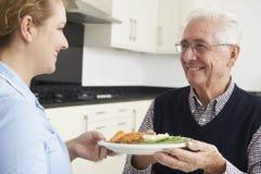 Betreuer-Umhüllungs-Mittagessen zum älteren Mann Stockbild
