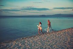 Betrieb des glücklichen Paars auf dem Strand im Sommer lizenzfreie stockfotografie