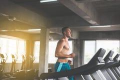 Betrieb des Sportgut aussehenden mannes auf den Tretmühlen, die Herz Training, querer geeigneter Körper und muskulös in der Turnh lizenzfreies stockfoto