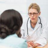 Betrokken arts die aan haar patiënt spreken Stock Foto's