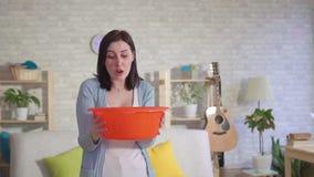 Betrokken vrouw die een emmer houden waar het water van plafond langzame mo stroomt stock footage