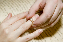 Betrothal. The man's hand dresses a ring on a female finger taken as close up Stock Photo