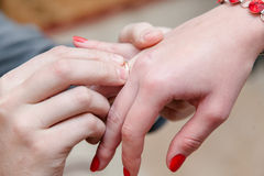 Betrothal. Hands newlyweds. The groom puts the ring on the finger of the bride. Macro shot of hands Stock Photography