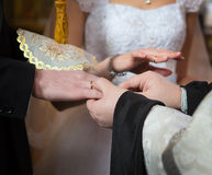 Betrothal. Priest changes rings on his fingers the married couple bride and groom Royalty Free Stock Images