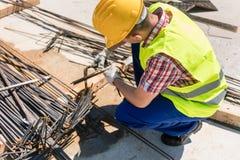 Betrouwbare arbeider die de kwaliteit van de staalbars controleren stock fotografie