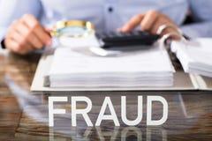 Betrugs-Text auf Schreibtisch stockbilder