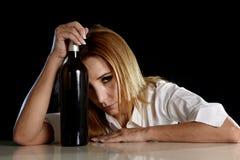 Betrunkene alkoholische blonde Frau allein, in deprimiertes vergeudet mit leidendem Kater der Rotweinflasche Lizenzfreie Stockfotografie