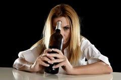 Betrunkene alkoholische blonde Frau allein, in deprimiertes vergeudet mit leidendem Kater der Rotweinflasche Lizenzfreie Stockbilder
