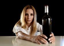 Betrunkene alkoholische blonde Frau allein, in deprimiertes vergeudet mit leidendem Kater der Rotweinflasche Stockbild