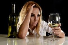 Betrunkene alkoholische blonde Frau allein im vergeudeten deprimierten Schauen durchdacht zum Weißweinglas Lizenzfreie Stockfotos