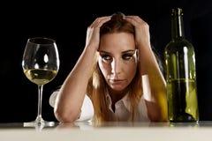 Betrunkene alkoholische blonde Frau allein im vergeudeten deprimierten Schauen durchdacht zum Weißweinglas Stockfoto