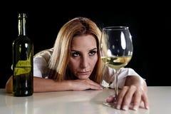 Betrunkene alkoholische blonde Frau allein im vergeudeten deprimierten Schauen durchdacht zum Weißweinglas Stockfotos