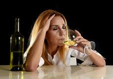 Betrunkene alkoholische blonde Frau allein im vergeudeten deprimierten Trinken vom Weißweinglas Stockbild