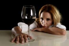Betrunkene alkoholische blonde Frau allein in vergeudetem deprimiertem trinkendem leidendem Kater des Rotweinglases Lizenzfreie Stockfotografie
