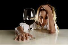Betrunkene alkoholische blonde Frau allein in vergeudetem deprimiertem trinkendem leidendem Kater des Rotweinglases Stockbild